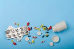 Geneeskundefles, blaarpak en pillenclose-up op blauwe achtergrond Stock Foto
