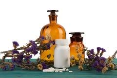 geneeskundeflessen op houten die lijst met bloem en pils wordt geïsoleerd stock afbeelding