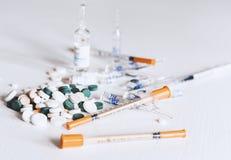 Geneeskundepillen of capsules met ampullen en spuiten op witte achtergrond met exemplaarruimte stock afbeeldingen