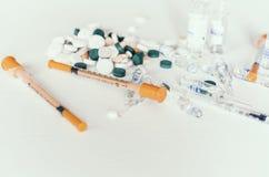 Geneeskundepillen of capsules met ampullen en spuiten op witte achtergrond met exemplaarruimte royalty-vrije stock afbeeldingen