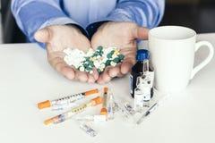 Geneeskundepillen of capsules met man'shanden op witte achtergrond met exemplaarruimte stock afbeeldingen
