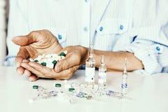 Geneeskundepillen of capsules met oude woman'shanden op witte achtergrond met exemplaarruimte stock afbeelding