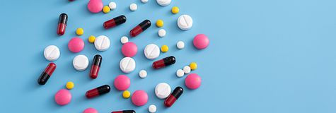 geneeskundepillen op blauwe achtergrondexemplaarruimte voor Geassorteerde tekst Stock Fotografie
