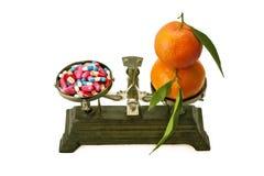 Geneesmiddel en mandarijnen op de schalen Stock Afbeelding