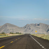 Geneigte Straße zur rechten Seite mit Bergen zum Horizont Stockbild