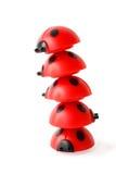 Geneigter Kontrollturm gebildet von fünf roten kleinen Marienkäfern Stockbilder