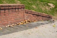 Geneigtes Abschlussstück der Stützmauer des alten Ziegelsteines, konkret mit Magnolienblättern lizenzfreie stockbilder