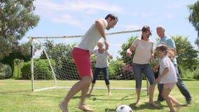 Generación multi que juega al fútbol en jardín junto metrajes