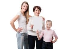 Generación tres de mujer que celebra al tablero en blanco Imagenes de archivo