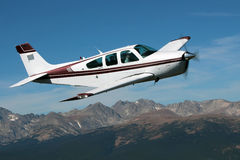 General Aviation - Beechcraft Bonanza. A Beechcraft Bonanza being piloted over the Rocky Mountains of Colorado. The plane is flying against a blue sky and clouds Stock Image
