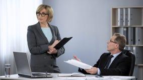 General manager som kritiserar kvinnlig anställd, stressigt arbete i företagskontor royaltyfri bild