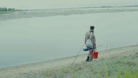 Fisherman on the road. The general plan of a fisherman walking along the river bank stock footage