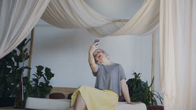General plan. A girl with white hair sits on the edge of a beautiful bed and picks up on the phone. Celphy woman in a stock video footage