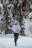 General plan older athlete running in winter woods in cold weather Stock Photography