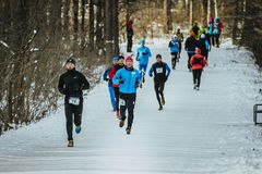General plan running through snowy Park alley group of men athletes Royalty Free Stock Photos