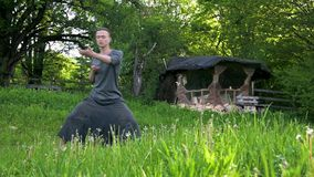 General plan a young man in Indian clothes and pants Aladdin practices qigong while doing exercises working with qi. Energy. in the summer outdoors next to an stock video