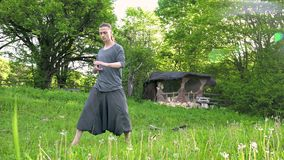 General plan a young man in Indian clothes and pants Aladdin practices qigong while doing exercises working with qi. Energy in the summer. outdoors next to an stock video