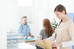 General practitioner during medical consultation. General practitioner in blue uniform with stethoscope during medical consultation with a patient royalty free stock photos