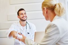 General practitioner gives medicament to patient. For treatment stock photo