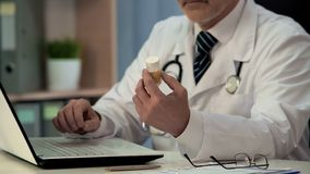 General practitioner searching instruction for new medicine online, health care stock image
