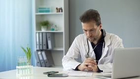 General practitioner studying medical records of new patient, health care system royalty free stock photo