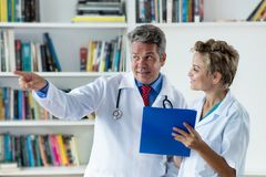 General practitioner talking about patient with female doctor. Hospital stock images
