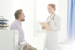 General practitioner talking to patient. General practitioner talking to a sick patient about treatment in the clinic royalty free stock image