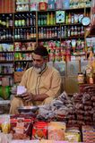 General store keeper tends to paperwork at Empress Market Karachi Pakistan. Karachi, Pakistan - February 22, 2015: A shop owner tends to paperwork while sitting stock photography