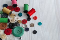 General top view of spools of thread and buttons on white wooden background. With copy space stock photos