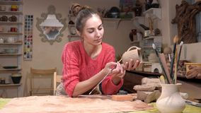 General view of a girl ceramist selecting a proper tassel to fine-tune the raw clay cup in the pottery workshop. stock video