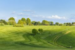 General view of a green golf course on a bright sunny day. Idyllic summer landscape. Sport, relax, recreation and Royalty Free Stock Image
