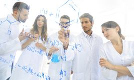 General-view seen trough a transparent board in a chemistry lab of people analyzing information royalty free stock photo