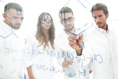 General-view seen trough a transparent board in a chemistry lab of people analyzing information Stock Photo