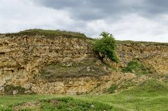 General view toward crag of sedimentary rock in the field Stock Photos