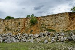 General view toward crag of sedimentary rock in the field Stock Photo