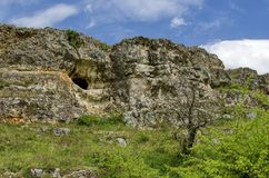 General view toward sedimentary rock with cave in the field Royalty Free Stock Images
