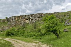 General view toward sedimentary rock with cave in the field Royalty Free Stock Photography