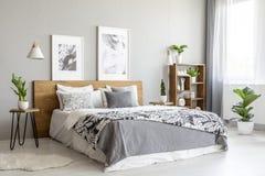 Generale modellato sul letto di legno nell'interno grigio della camera da letto con le piante ed i manifesti Foto reale fotografie stock libere da diritti