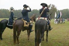 Generalen George Washington och personal förbereder sig att salutera kolonnen av kontinentala patriotsoldater på kapitulationfält Royaltyfri Bild