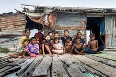 Generatie drie van Bajau-stam zit buiten hun houten hut Stock Afbeelding
