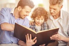 Generatieportret Grootvader, vader en zoonszitting en lezing een boek op bank Stock Foto's