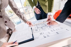 Generating the architectural project. Three architects consider the drawing of the building. Architects spend hands in the drawing stock photography
