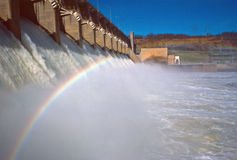 Generating hydro-power. Dam generating electricity to the grid with a rainbow in the mist of the spillway stock images