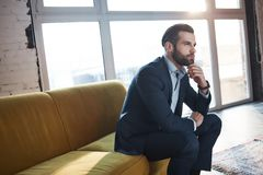 Generating ideas...Confident and handsome young businessman is thinking about business while sitting on the sofa in his. Modern office. Fashion look. Business royalty free stock images