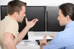 Generating new ideas. Two young businessmen talking about business while sitting in front of computer monitors royalty free stock photo