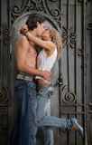 Generation. Kiss of young beautiful couple on a background of an old gate Royalty Free Stock Photos