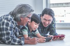 Generation drei von männlichem lernt, Handyinternet tohether zu benutzen stockfotografie