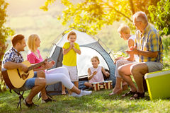 Generation family playing a guitar and singing. On camping stock photo