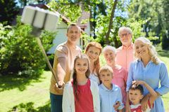Happy family taking selfie in summer garden. Generation and people concept - happy family taking picture with smartphone and selfie stick in summer garden royalty free stock photography