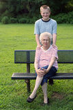 Generation Portrait. Smiling teenage grandson standing behind his grandmother, sitting on a park bench royalty free stock photos